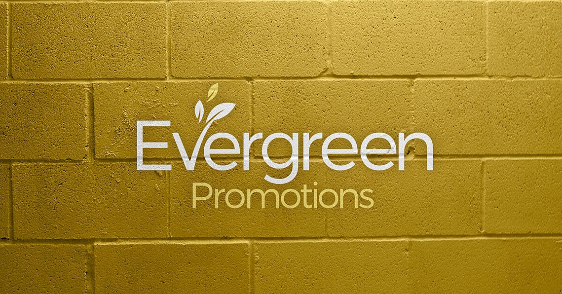 EverGreen Promotions Logo on a yellow brick wall.
