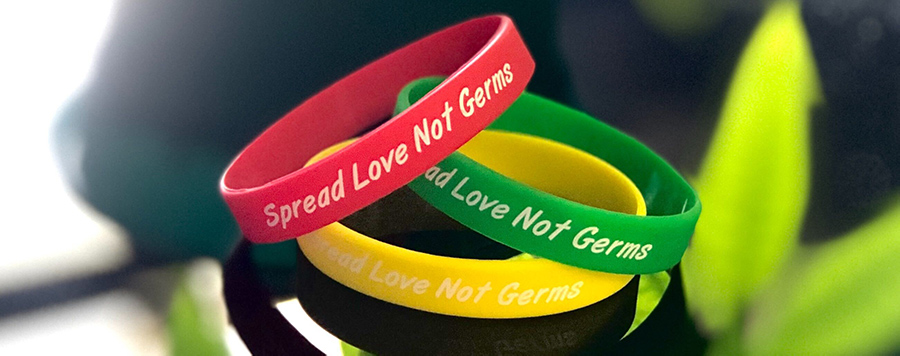 "Red. Green, and Yellow wristbands that read ""Spread Love Not Germs"""