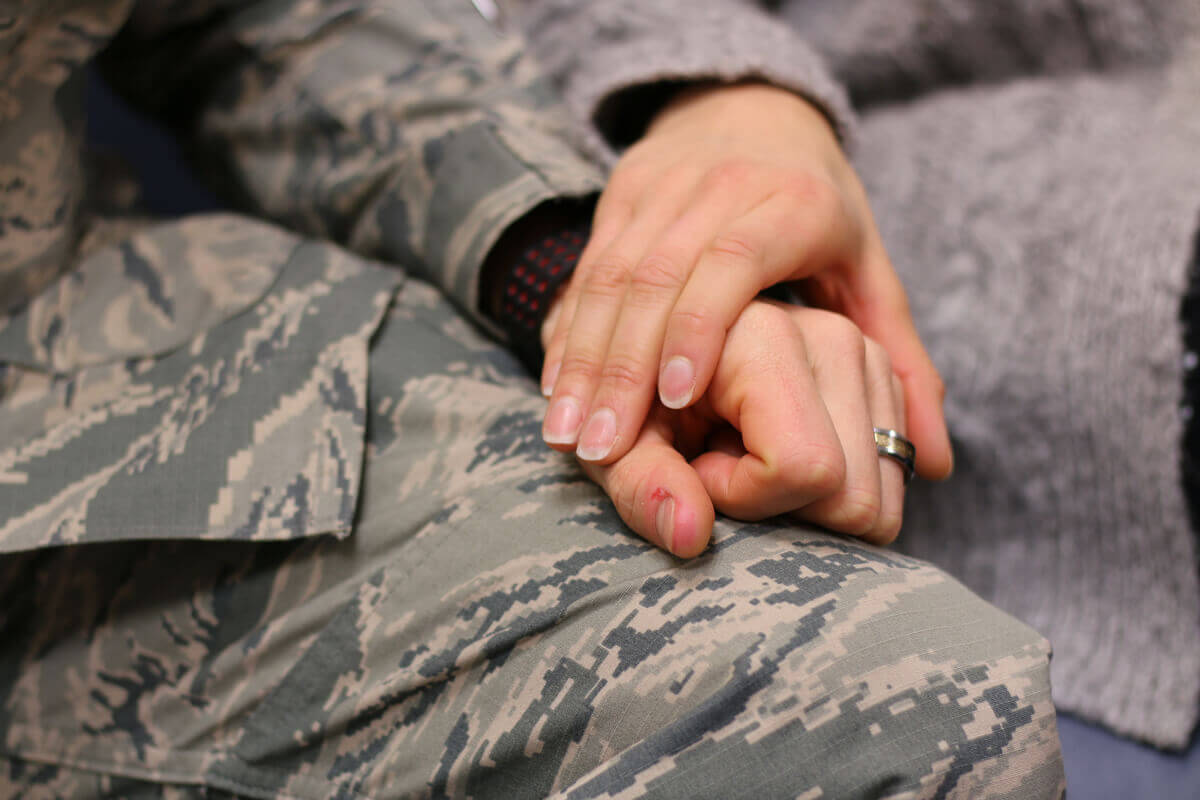 soldier holding a friends hand.