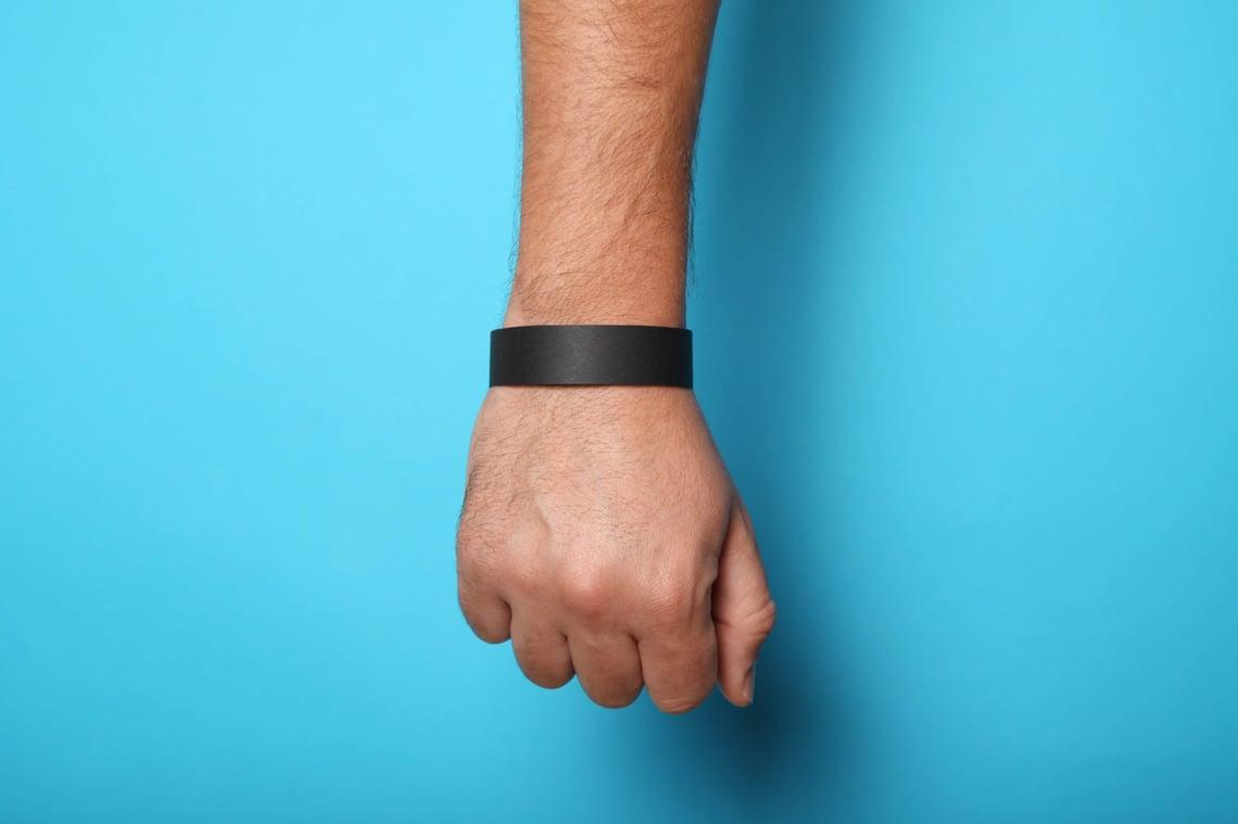 An individual wearing a black wristband.