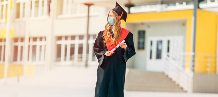 A lone woman wearing her graduation robe and cap and a facemask.