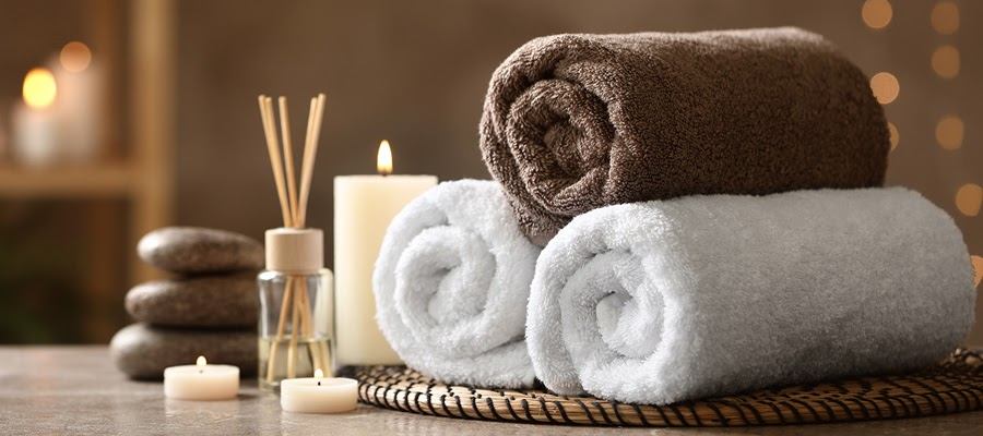 Towels, hot stones, and candles at a spa or massage parlor.
