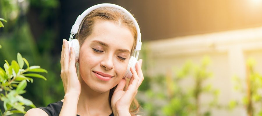 A happy woman listening to music on hearphones