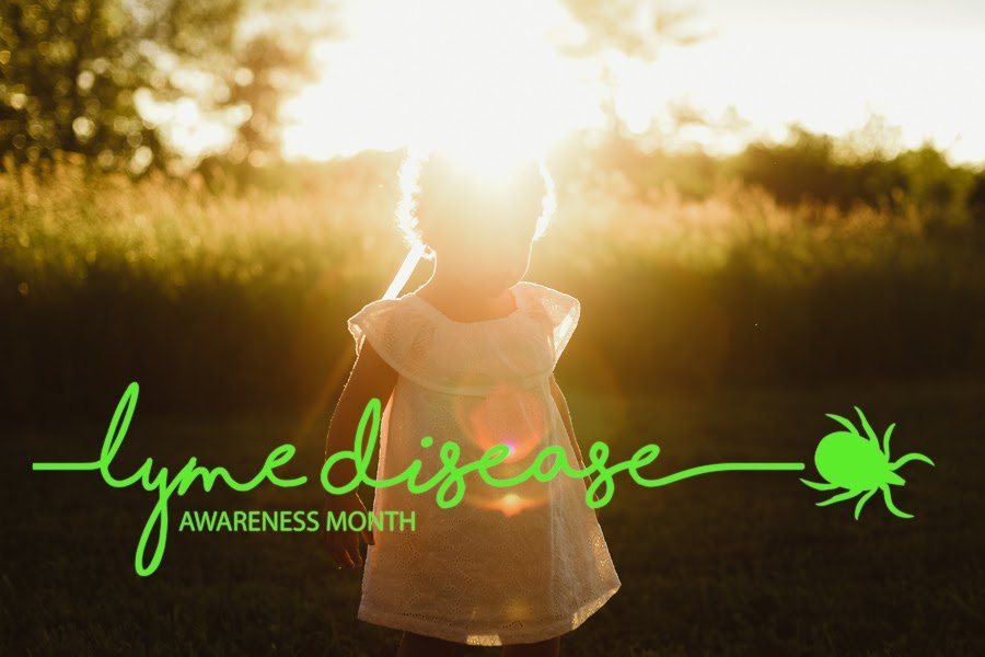 "A little girl playing in a field near high grass. The words ""Lyme disease awareness month"" in green"