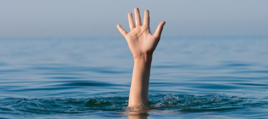 A drowning man waves his hand for help