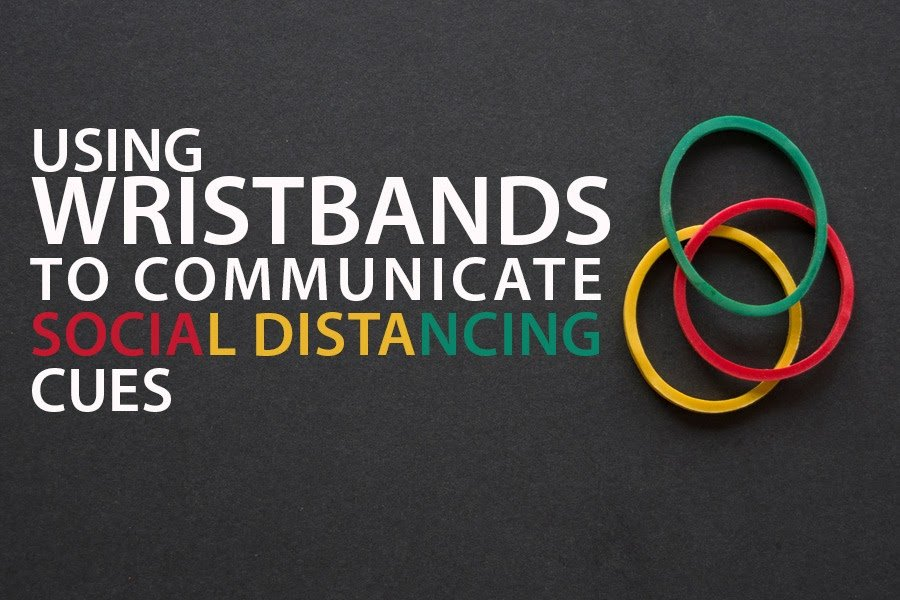 "Black background with 3 wristbands. Text reads ""Using wristbands to communicate social distancing cues."""